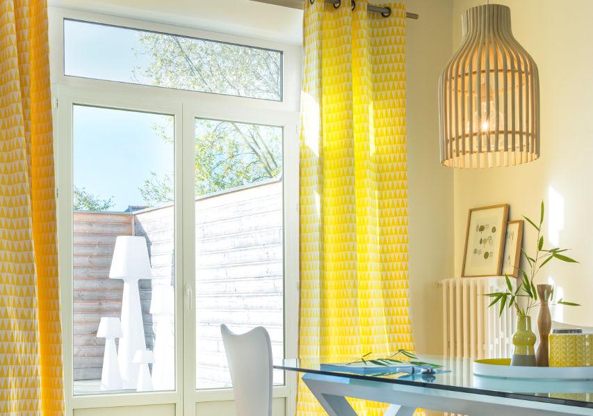 Photo d'illustration d'une porte-fenêtre Élisa dans un salon avec des rideaux jaunes